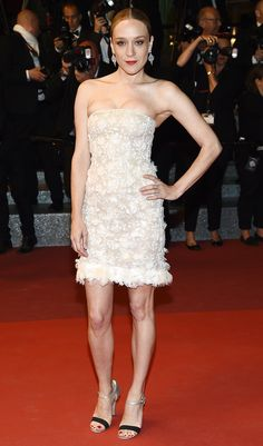 CHLOE SEVigni  in a beige strapless dress with white lace pattern and a feathered hem