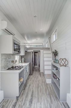 A white farmhouse sink, four burner cooktop, over the range microwave/venting hood, and full size refrigerator make the kitchen as functional as it is beautiful.