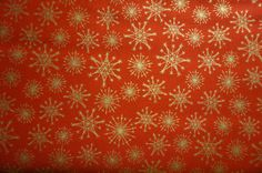 Gold Snowflakes (Metallic on Red background); sold by the yard