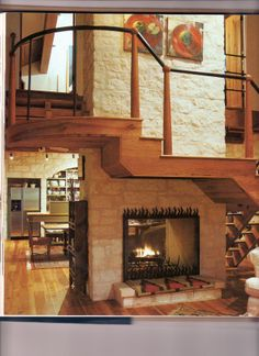 I love this - stairs wrap around the fireplace which makes good use of the deadzone under the stair, creates a central unifying architectural element, AND allows the staircase to be longer so that there are only 2-3 steps between landings (great for our aging bodies that still want to climb stairs)