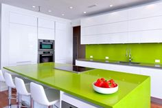 Ultra modern kitchen with sleek white cabinets and lime green island and backsplash.