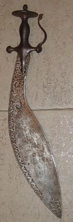 A Tulwar Hilted Indian Kukri with 17' carved blade depicting warriors and floral work borders, iron hilt with disc pommel and dragon head side guard. Early 19th century.