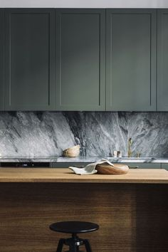 Gorgeous kitchen with sage cabinets and grey marble slab backlash and wood island