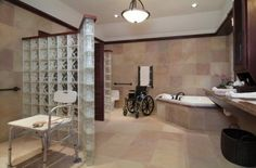 """Beautiful accessible bathroom. The wheelchair bound client needed accessibility but did not want it to be obvious. A masculine feel with spa-like quality was desired. Walls needed to come down to provide a luxurious roll-in shower and side entry toilet. Direct access to the sinks was allowed when storage shifted to the side and the counter top was floated on the wall. A reddish toned slate, """"painted desert"""" was used on the walls and floor to continue the exterior brick wall color into the bath."""