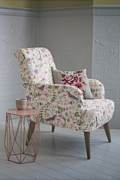 Make a bold statement in your living room with a floral patterned armchair and contrasting floral cushion.