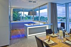 Futuristic Kitchen Design Interior With Blue Led Lighting Set On White Kitchen Backsplash As Well Round Pendant Lamp And Wooden Dining Table I The Near As Well Wide Glass Wall Beautiful Lights Decors Ideas for Special Moment Home decoration http://seekayem.com