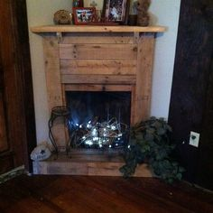 Faux Pallet Fireplace - not a fan of the lights but a few candles (safely placed) would be great! Pallet Fireplace, Faux Fireplace Mantels, Fireplace Garden, Rustic Fireplaces, Fireplace Surrounds, Fireplace Ideas, Country Fireplace, Cottage Fireplace, Fireplace Bookshelves