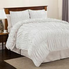 """Ruched comforter set in white.     Product: Queen: 1 Comforter, 2 standard shams and 1 bed skirtKing: 1 Comforter, 2 king shams and 1 bed skirtConstruction Material: PolyesterColor: WhiteFeatures:  Ruching detailsBed skirt has a 14.5"""" drop Dimensions: Standard Sham: 20"""" x 26"""" Queen Comforter: 90"""" x 92""""King Sham: 20"""" x 36""""King Comforter: 102"""" x 92""""  Note: Shams do not include inserts  Cleaning and Care: Dry clean"""