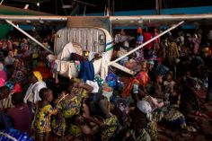 CROWDED: People waiting for evacuation flights settled in for the night inside an airport hangar in Bangui, Central African Republic, Sunday. (Rebecca Blackwell/Associated Press)