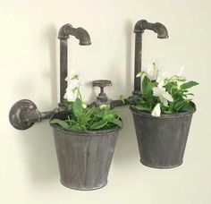 "Double metal planter features a weathered metal finish and two faux faucets with a spigot handle in the middle. This is made from plumbing parts and looks great mounted on a fence. 7"" flower pots are                                                                                                                                                                                  More"