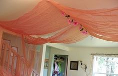 You may be able to use ceiling hooks to  tie a piece of ribbon or thin cording  and drape tulle through.