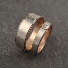 "A custom request based on my lines and granules ring. It is two bands, one at 1/4"" wide, the other at 1/8"". Each features three equal sections with two lines framing 14k gold granules. The wider ring has three granules in each section, the narrower band just one. The rings are in sterling silver with a 14k rose gold lining."