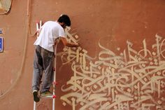 Yazan Halwani travaillant sur sa fresque de Fairuz à Gemmayzé