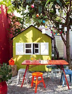 Fifi Mandirac, jardin Fifi Mandirac, jardin couleur, court couleur, table rouge, tabouret orange, tabouret bleu, cabane, cabane verte, court galets
