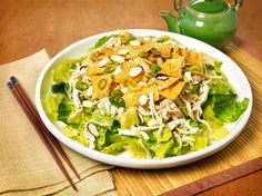 Feast from the East Chinese Chicken Salad. 1 medium head iceberg or romaine lettuce, shredded; 1/2 cup sliced green onion; 1 bunch cilantro, chopped; 1/4 cup thinly sliced celery; 1 lb cooked chicken breast, shredded. Combine ingredients in a large bowl. Toss with Feast From the East Sesame Dressing (Costco) to taste. Sprinkle with 1 pkg (3-oz) fried won ton strips and 1/4 cup slice almonds or 1/4 cup chopped unsalted dry-roasted peanuts. Optionally add 1/2 cup char siu pork, julienned.