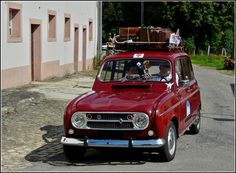 A well-preserved Renault 4 with luggage on the roof.