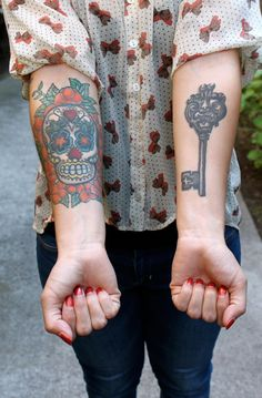 Calavera and key tattoos.  The calavera is beautiful.  The key is cliche.  In my opinion.  Some would say the same about calavera tattoos, but a skull decorated with flowers is ALWAYS going to be way cooler than a key.
