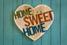 Home Sweet Home message wooden heart from recycled old palette on turquoise painted background copy space