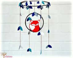 This mobile is sure to capture anyones attention and this gorgeous felt fox mobile moves at just the slightest air movement!  You will receive a mobile consisting of 1 sleepy fox perched on a hoop surround by leaves. Colors represented in the photos are Peacock, marine, smoke, and parchment leaves with the fox in orange and white. I have wrapped the hoops in chocolate brown ribbon to look like branches. MEASUREMENTS: ============== Large hoop width: 8 Small hoop width: 5  UPGRADE TO A…