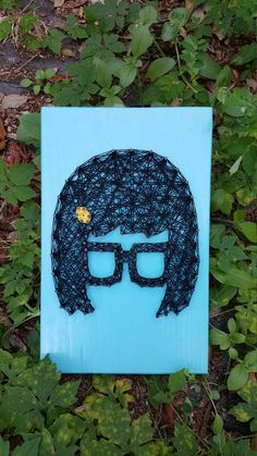 Uhhhhhhhhhh.  This is a String Art of the infamous Tina Belcher from Bobs Burgers. The board is approximately 7 X 12 inches.  Each board is made to order so you will not be receiving the exact pictured piece. That being said please keep in mind that we try to make each piece as closely to the pictured item as possible but shade and exact placement of the nails may vary. This is what makes each item unique and gives it character.  By default, boards do not come with hanging hardware attached…