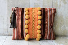 This zip clutch has been hand made using reclaimed textiles. The exterior is a vintage fabric with a woven ethnic-inspired design throughout.  The front