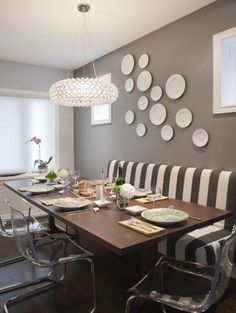 Love the mix of the acrylic chairs and the  striped settee