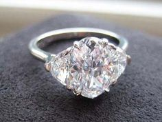 Three Stone Ring with 2ct Oval Diamond and Half Moon Side Stones  by Leon Megé