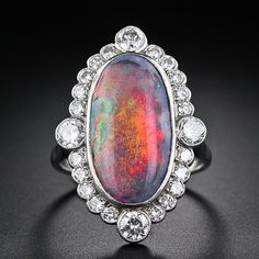 This amazing gemmy black opal must be seen to be believed! The mesmerizing, elongated oval, black opal and diamond ring is ablaze with the rare and coveted prominent colors of fiery red and orange, with secondary flashes of blue and green. The iridescence is so strong that the opal drastically changes colors from every different angle! This gorgeous gem is beautifully presented in a platinum and diamond Edwardian style ring dating back at least a few decades.