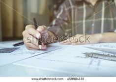Architect or engineer working on blueprint, Construction concept. Engineering tools.Vintage tone retro filter effect,soft focus(selective…