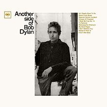 A black-and-white photograph of Bob Dylan standing with his foot raised, surrounded by thick white borders