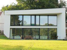 Villa minimaliste sur versant - Villa minimaliste dont la volumétrie est dictée par les limites parcellaires obliques et le souci d'avoir un impact minimal sur l'étroite voirie publique.