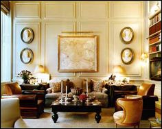 Adore the rolled-arm wooden chairs. And the molding on the walls. And the bookcase. Etc