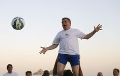President of the International Olympic Committee (IOC) Thomas Bach (top) is helped by Brazilian national rugby players on Barra da Tijuca beach in Rio de Janeiro, Brazil, August 4, 2015. Bach met with current and former Brazilian Olympians during the event. Rio de Janeiro marks the one-year countdown to hosting the Rio 2016 Olympic Games on Wednesday. REUTERS/Sergio Moraes