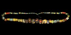 ANGLO-SAXON POLYCHROME BEAD NECKLACE 6th-7th century AD  A restrung necklace of glass beads of mainly spherical, barrel-shaped and tubular types, many with mosaic glass inserts or appliqués. 81 grams, 27cm