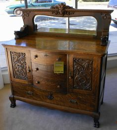•Description-Solid oak hand carved medium oak bow front center buffet with attached beveled mirror and paw feet circa 1900