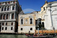 Photo taken in an old palace and a church in Venice, Italy. In the image, taken from the Grand Canal seen, between the water and the deep blue sky a gondola pushed by classic gondolier, from left to right, a part of the important palace facade with columns, a small building with a coat of arms and part of the facade of the church of Santa Lucia.