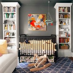 Liking the gray walls with the white book cases, dark crib over a navy/white pattern rug.
