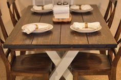"""James+James 5.5'x37"""" Trestle Table with a traditional top, stained in Dark Walnut with an Ivory Painted Base. Pictured with X-Back dining chairs."""