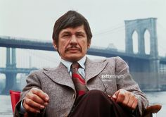 Publicity handout from Death Wish shows Charles Bronson seated on the banks of the East River with the Brooklyn Bridge in the background. 1974.