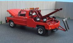 1972 F350 Wrecker Model. The wrecker bed and wrecker unit are made from tin beer cans and brass. Boom raises and lowers, boom telescopes, pulleys work, winch works, double rubber sling works, tow bar also moves and moves side to side, dollies are removable from the bed and can be assembled, tool box opens, remote bed handles also move and upper rear bed eyelets move. A model car can be hooked up to the tow bar with the J-hooks. All lights on the bed are also scratch built.