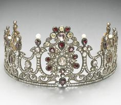 An antique diamond, garnet and silver topped gold tiara, circa 1850, of openwork design and closed-back setting, centering a rose-cut diamond within a starburst surround of smaller rose-cut diamonds, accented by pear-shaped garnets and surmounted by a rose-cut and light yellow old mine-cut diamond cluster, the remainder of tapering garland design set throughout with rose-cut diamonds, accented by pear-shaped garnets and (later) cultured pearls.