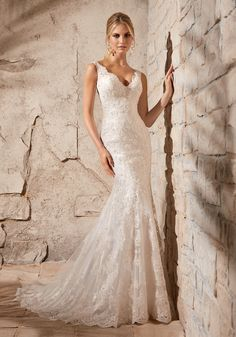Romantic and feminine, this Lace Bridal Dress is the epitome of chic. The beautiful open back is accented with delicately beaded scalloped lace, and covered buttons