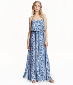 Maxi dress in woven viscose fabric with a printed pattern. Wide flounce at top, narrow adjustable shoulder straps, opening at back of neck with button, and elasticized seam at waist. Slits at sides.