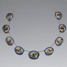 MICROMOSAIC NECKLACE, CIRCA 1800 Composed of nine oval plaques each depicting historic architectural  views in and around Rome, including; the Temple of Vesta, the Temple of Sybil at Tivoli and the Pyramid o Cestius, to a fine trace link chain, each inset to a blue glass tablet, length approximately 600mm.