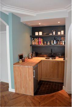 """Dans ce petit coin cuisine imbriqué dans une recoin du séjour, le noir mat a été choisi pour renforcer le côté """"niche"""", tandis que le bleu-vert lumineux apporte de la couleur et fait le lien avec le reste de la pièce. De larges étagères ouvertes au mur servent pour le rangement des aliments."""