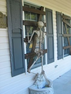 cardboard affixed to window to make it look boarded up and skeleton proped to look like it's trying to get in.