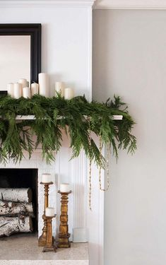 I love how free and natural this mantle greenery looks. The simple white candles… I love how free and natural this mantle greenery looks. The simple white candles layered into the greenery create a simple and laidback Christmas look.