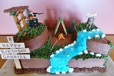 """My grandson wanted a hunting and fishing cake.  I used a 9X13 base and then an 8"""" round cut in half for the two sides.  Those little rocks are yogurt covered raisins and the tree stand and tent are made from graham crackers and pretzels!"""