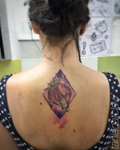 Sketchy strawberry tattoo on the upper back.