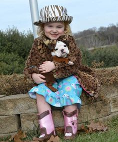 Little girl with english bulldog puppy in arms